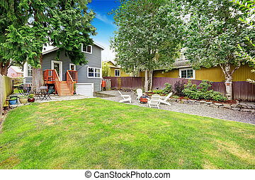 Fenced back yard with patio area and white adirondack...