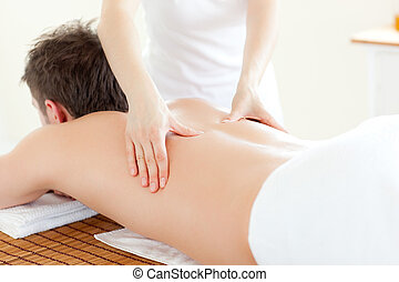 Caucsasian young man receiving a back massage in a Spa...