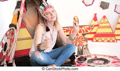 Model with tambourine dancing while sitting at wigwam -...