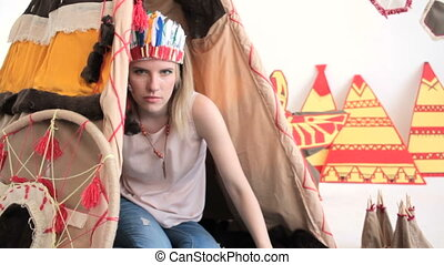Young blonde girl in native American Indian costume crawling...