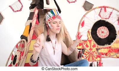 Model with tambourine dancing while sitting at wigwam