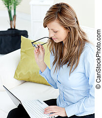 Attractive woman using a laptop sitting on a sofa at home