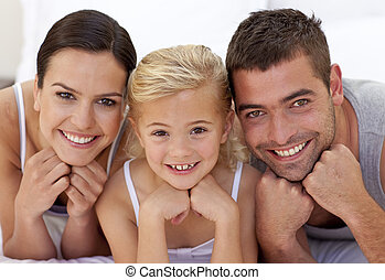 Cute little girl with her parents lying on a bed at home