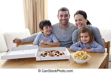 Young family eating a pizza in the
