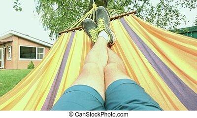 Legs of man swinging in hammock 4K video, bleached colors -...