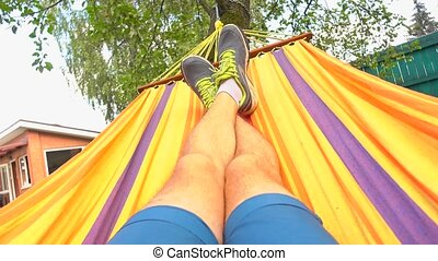 Man in running shoes swinging in hammock 4K video - Man...
