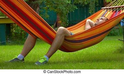Man having rest in bright hammock 4K video