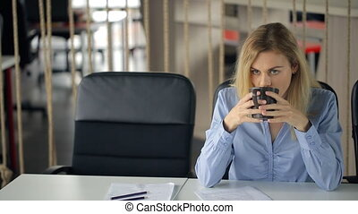 Pretty blonde woman sits at table in office and drinks coffee.