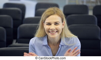 Pretty blonde woman sits in conference hall and cheerfully...