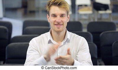 Blonde man happily claps his hands in conference hall. He is...