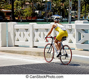Young Woman Bike Racer - Young woman in racing gear riding...