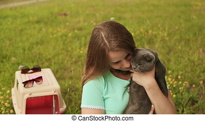 A girl holds a Scottish Fold cat.