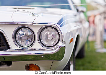 Headlights of old white american muscle car with chrome...