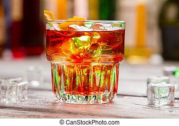Glass with dark orange beverage.