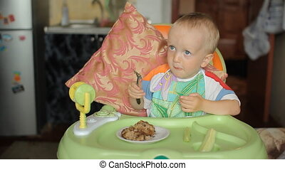 Beautiful blond baby boy sitting at a table and eating...