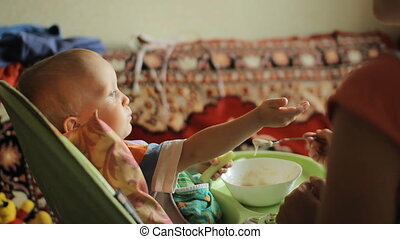 Beautiful blond baby boy sitting at the table and eats milk...