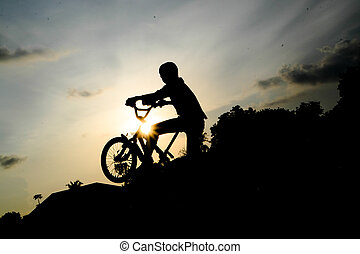 Silhouette Boy - Boy cycling at sunset