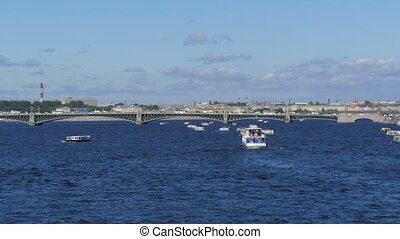 A large river in St.Petersburg, ships float down the river on a sunny day.