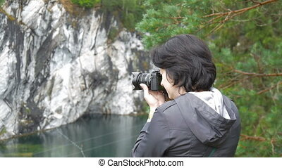A woman photographs the beautiful landscape in the Karelia