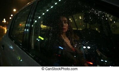 Beautiful brunette girl behind car window at rainy night