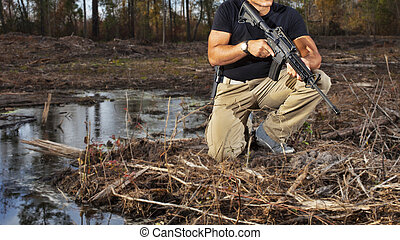 Waterside guard - Man with an AR-15 and handgun kneeling...