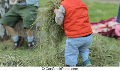 Boy playing with other children and hay. He picks up and throws hay to another location