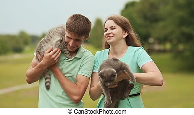 Guy and girl play with the Scottish Fold cat and gray British cat