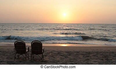 Two chairs near coastline at sunset time
