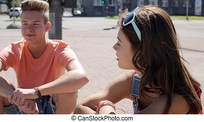happy teenage couple talking on city street - summer...