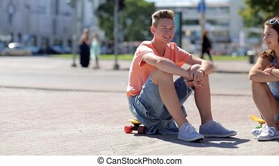 teenage couple with penny boards talking in city - summer...