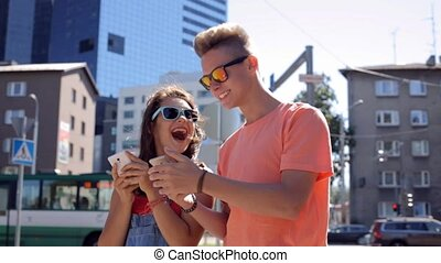 happy teenage couple with smartphones in city