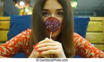 Brunette girl holding red lollipop - Cute girl sitting in a...