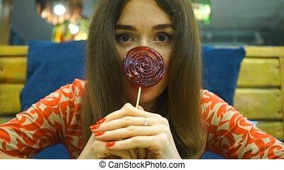 Brunette girl holding red lollipop