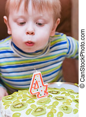 boy blows out the candles on the cake birthday four years