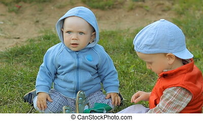 Two baby boys playing together on the lawn in the park.