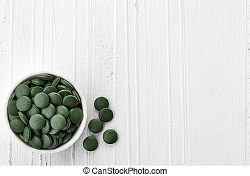 Spirulina algae powder and tablets on white wooden...