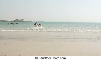Happy man and woman swimming on the beach