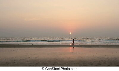 Beauty woman relaxing on the Goa beach in sunset rays