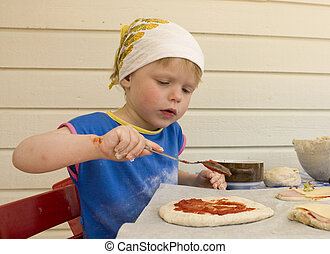 Small girl (3 years old) making a pizza.