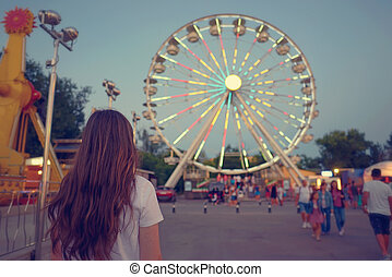Teen girl at park of amusement, dreamy summer time