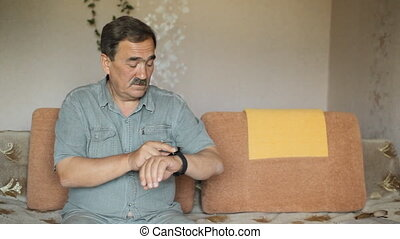 Senior man touching smart watches. He is sitting on the sofa at home and check messages