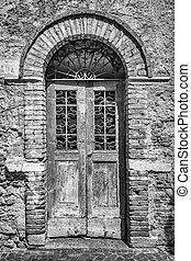 Old wooden door with brick archway.