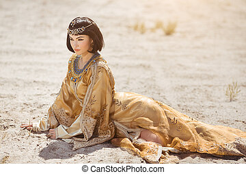 Beautiful woman like Egyptian Queen Cleopatra laying in...