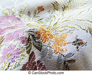 Shiny brocade textile or cloth with floral pattern, close-up...