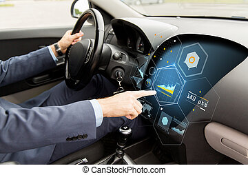 close up of man driving car with diagram on screen -...