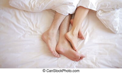 a man and a woman in bed. male and female legs top view,...