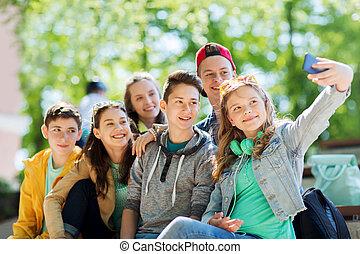 happy teenage students taking selfie by smartphone -...