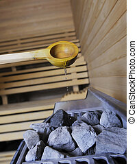 hot stones and splashing water in sauna - wooden luxury...