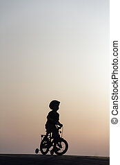 silhouette of a boy on bicycle