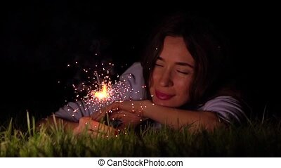 Romantic thoughtful girl laying on the grass with burning sparkler at night. Super slow motion video shot at 500 fps